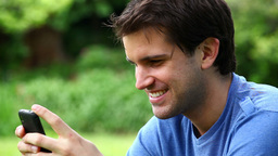 Smiling man using a mobile phone Footage