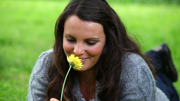 Smiling brunette smelling a yellow flower Footage