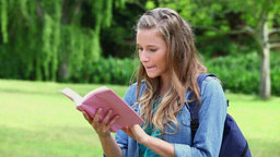 Smiling young woman looking at a book Footage
