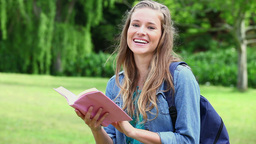 Smiling young woman looking at a book Stock Video Footage