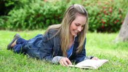 Blonde woman reading a novel Stock Video Footage