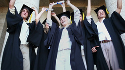 Happy graduated students raising their arms Footage