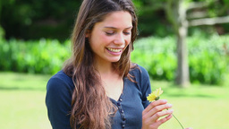 Brunette woman holding a yellow flower Footage