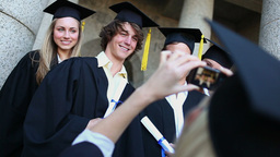 Smiling graduated students being photographed Stock Video Footage