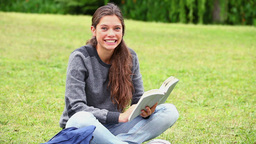 Happy young woman reading a fascinating novel Footage