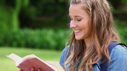 Happy woman reading a fascinating book Stock Video Footage