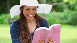 Happy brunette reading a book Stock Video Footage