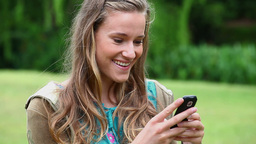Happy young woman typing on her cellphone Stock Video Footage