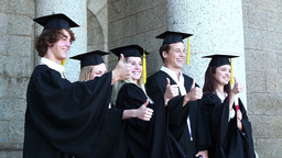 Graduates posing the thumbsup Stock Video Footage