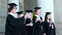 Graduates posing the thumbsup Footage