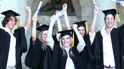 Happy graduates raising arms and jumping Footage