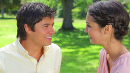 Smiling couple sitting on the lawn Stock Video Footage