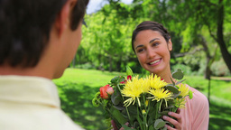 Smiling woman receiving a bunch of flowers Footage