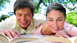 Happy couple reading novels together Stock Video Footage
