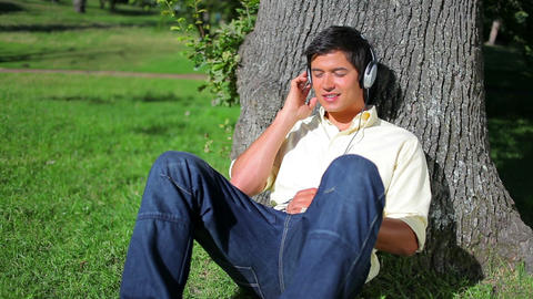 Peaceful man leaning against a tree while listenin Footage