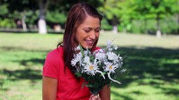 Happy woman laughing while holding flowers Stock Video Footage