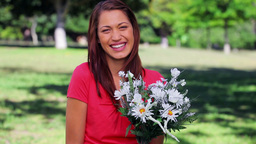Happy woman laughing while holding flowers Footage