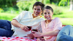 Happy couple sitting on a blanket while drinking red wine Live Action