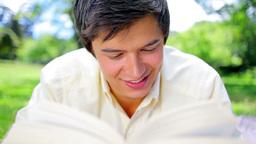 Smiling man reading an interesting novel Footage