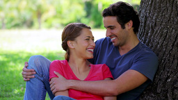 Smiling couple leaning against a tree Footage