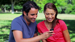 Smiling couple looking at a text on a cellphone Stock Video Footage