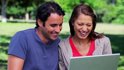 Happy couple looking at their laptop Stock Video Footage