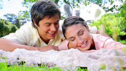 Smiling man looking at his girlfriend napping Live Action