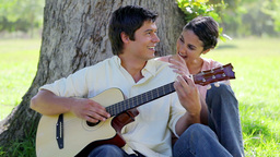 Laughing man playing a guitar for his girlfriend Live Action