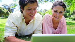 Smiling couple using their laptop Stock Video Footage