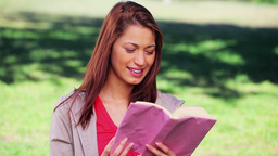 Happy woman reading an interesting novel Footage