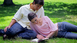 Happy woman reading a book near her boyfriend Live Action