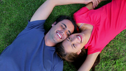 Happy couple resting while lying on the grass Footage
