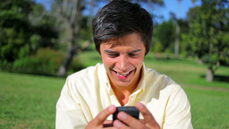 Smiling man texting on his cellphone Footage