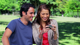 Smiling couple looking at a digital camera Footage