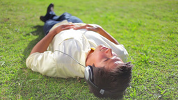 Peaceful brunette man lying on the grass while lis Stock Video Footage
