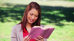 Cheerful woman reading an interesting novel Live Action