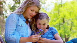 Mother and daughter using a magnifying glass Footage