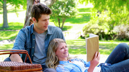 Woman reading a book while leans on her husband Stock Video Footage