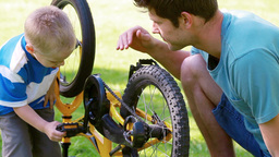Boy turning a wheel with his father Footage