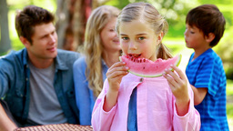 Girl eating a watermelon with her family in backgr Footage