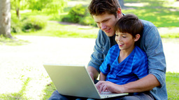 Boy on his fathers tigh using a laptop Footage