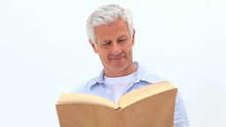 Smiling man reading a novel Footage
