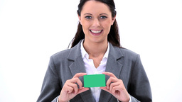 Smiling brunette woman holding a business card Footage