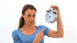 Woman points at a clock then open her mouth in sur Stock Video Footage