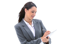 Brunette businesswoman writing on a clipboard Stock Video Footage