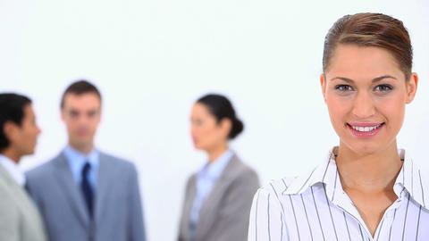 Businesswoman looking at camera with colleagues in Footage