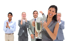 Woman holding a trophy with coworkers applauding Stock Video Footage