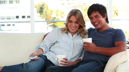 Smiling couple relaxing while watching the televis Footage