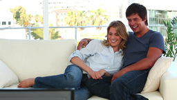 Couple laughing while watching the television Stock Video Footage