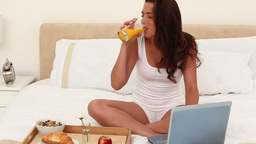 Smiling brunette eating her breakfast Stock Video Footage